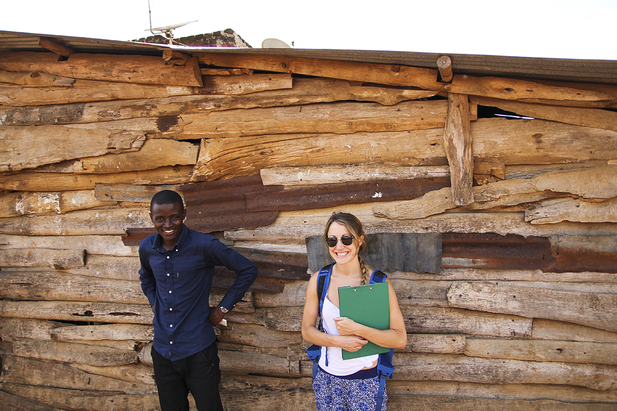 Alyse Daunis with Hashim Mutanje outside log building