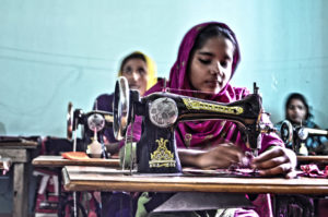 Young garment workers sew fabric in Bangladesh.