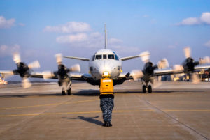 Navy airman signals P-3 Orion plane