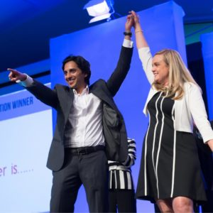 Students celebrating a business pitch competition win, arms raised