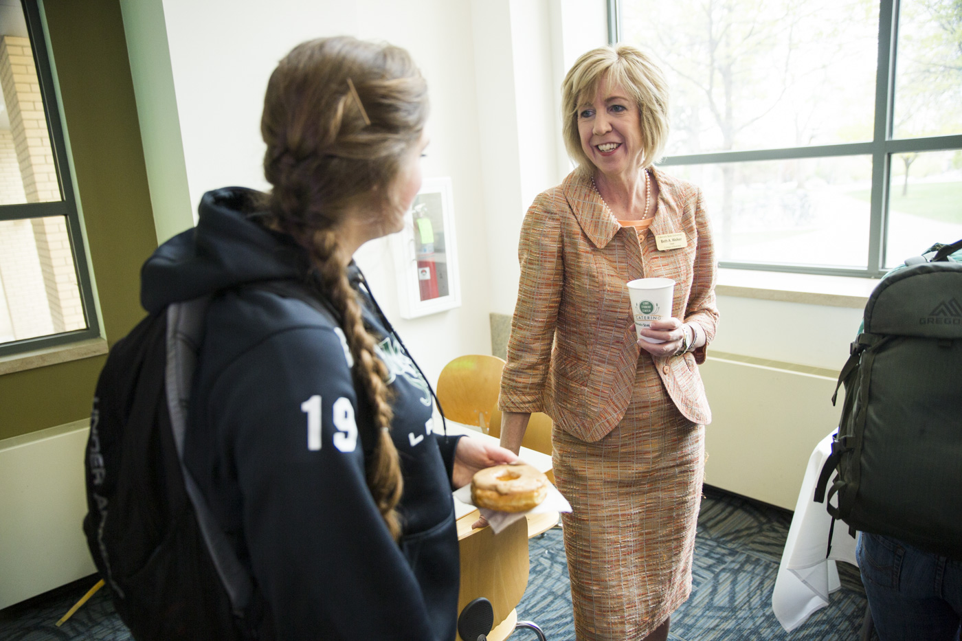 Dean Beth Walker talks with students, sharing coffee and donuts.