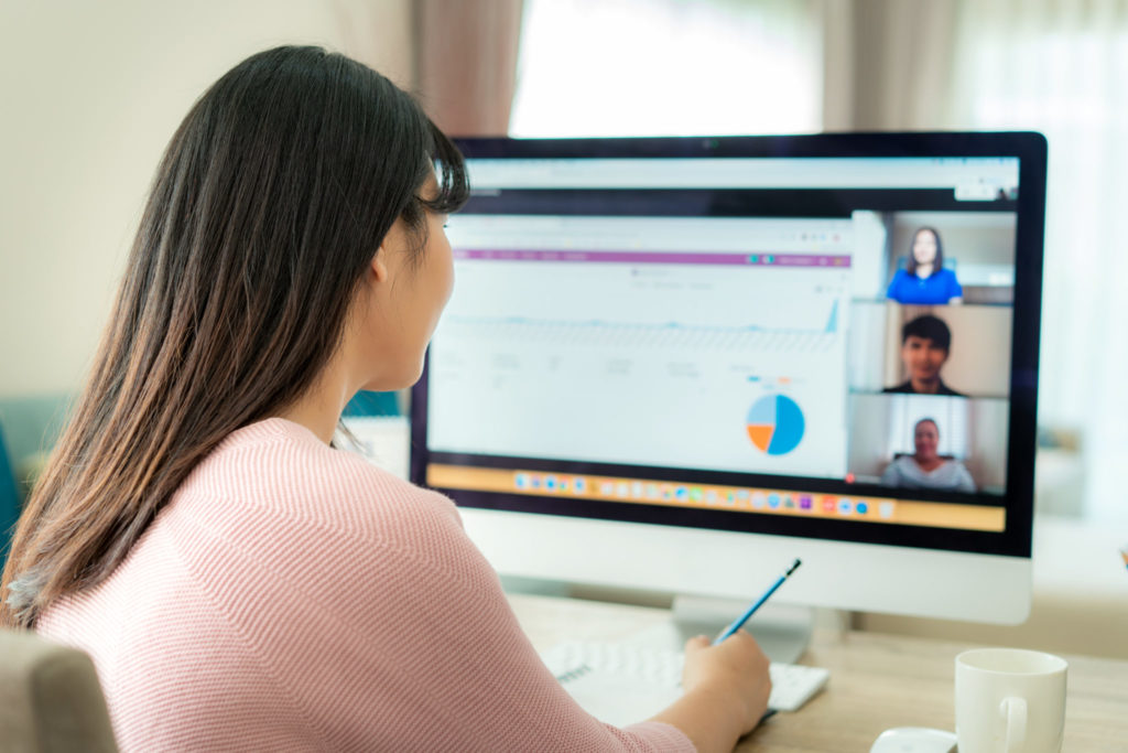 A woman participating in a video conference while working from home