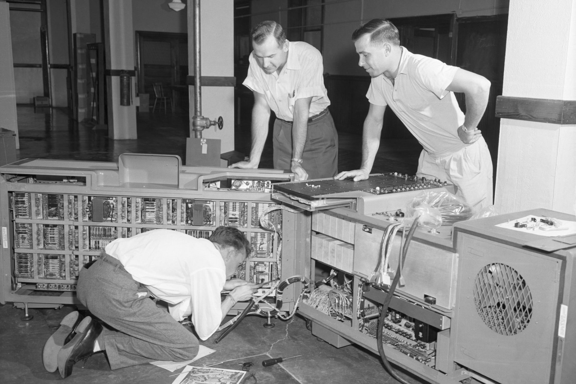 Photo of a new computing machine being installed in the basement of the Business Economy Building on July 10, 1958.  On the envelope are the names: Wayne Thomas, Engineer for Burroughs Corporation, Ken Whitcomb and Dr. Elmer Remmenga, but they don't specify which person is whichin the images.