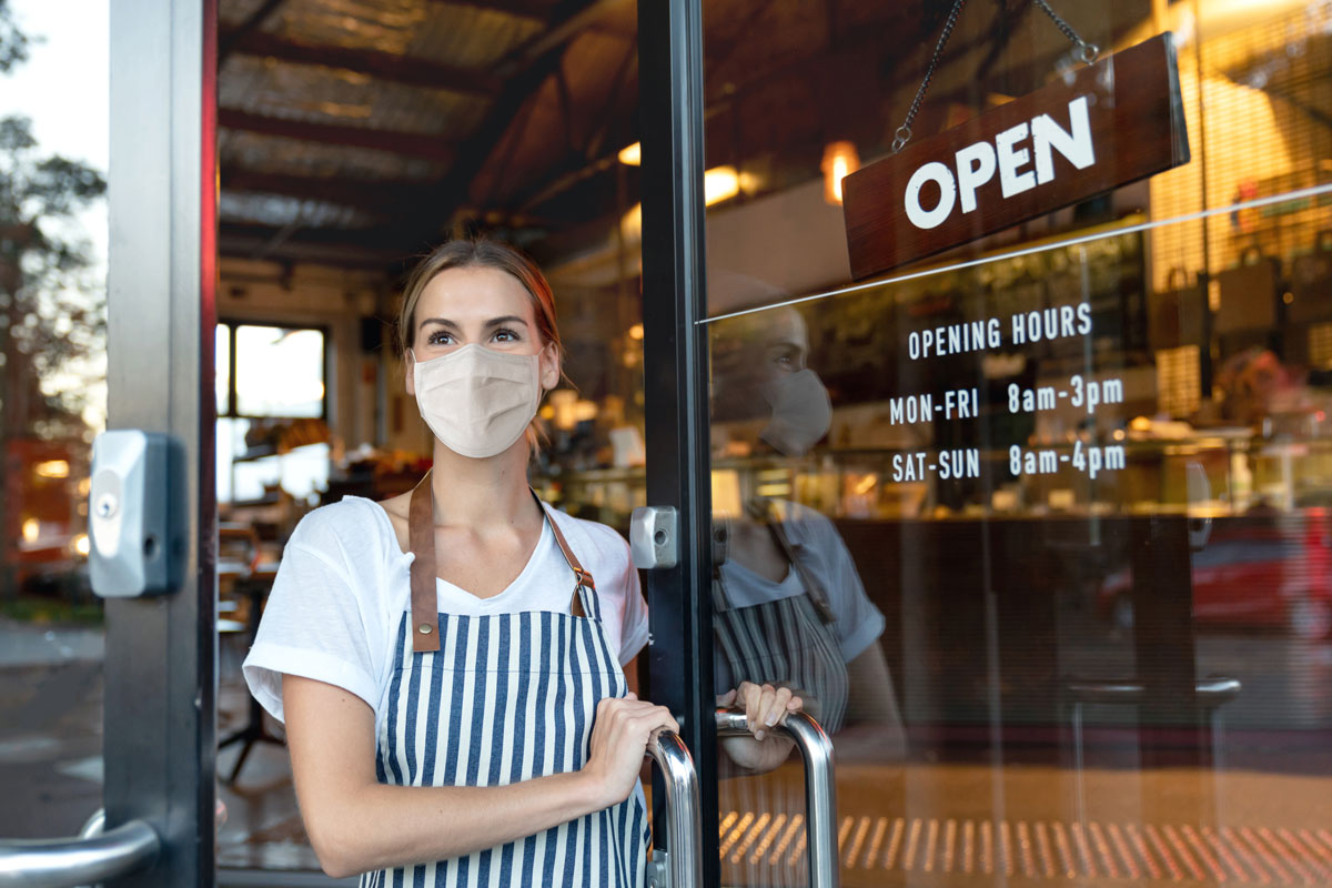 A female business owner stands at the door to her shop