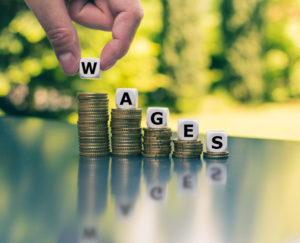 Wages spelled out on decreasing stacks of coins