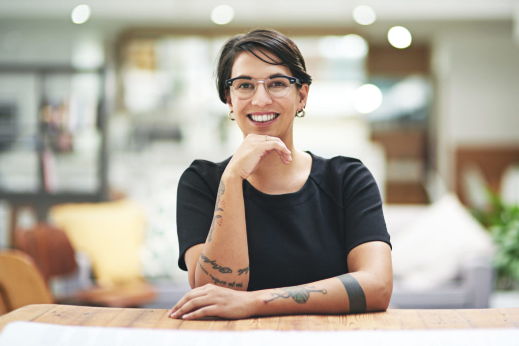 photo of a woman at work with tattoos on her arms, smiling and resting her head on one hand