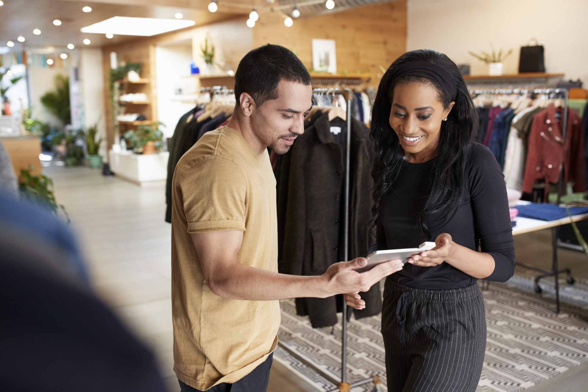 Retail manager and employee look at a tablet inside clothing shop