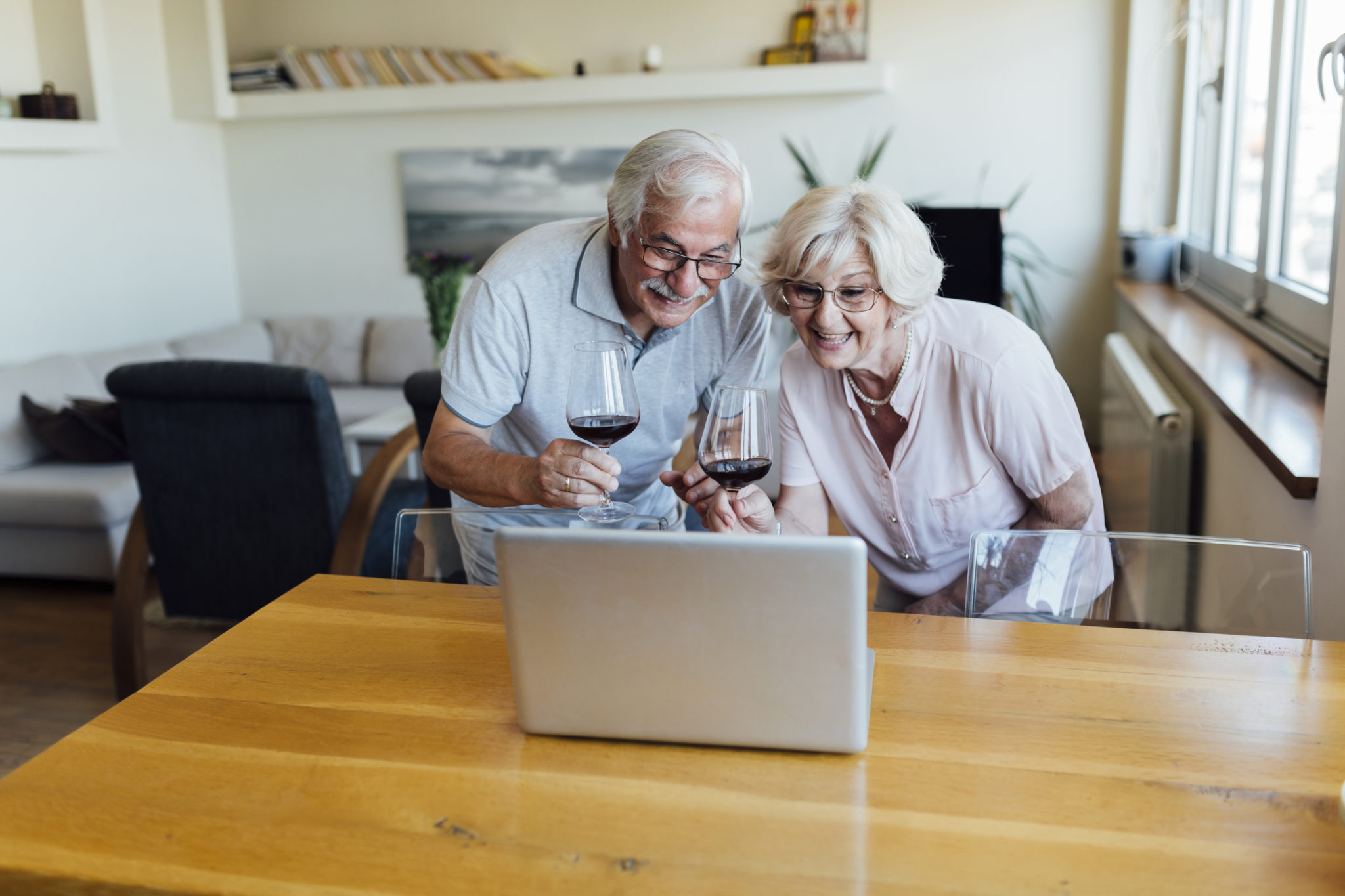 An older couple drinks wine in front of a laptop
